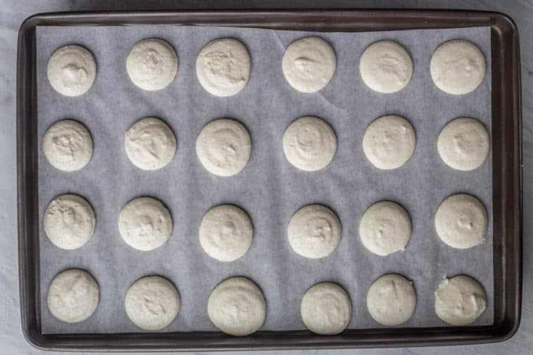 How to pipe the macaron batter into macarons on a baking sheet.