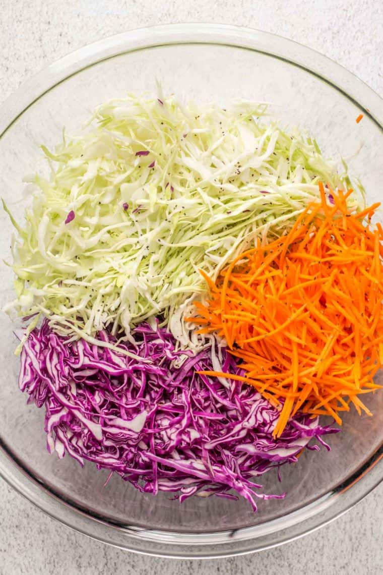 A glass bowl filled with shredded cabbage, red cabbage, and carrots.