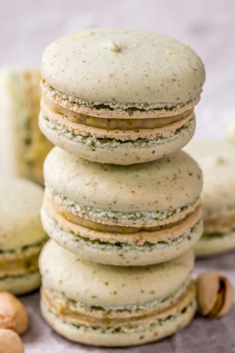Three pistachio macarons stacked on top of each other.