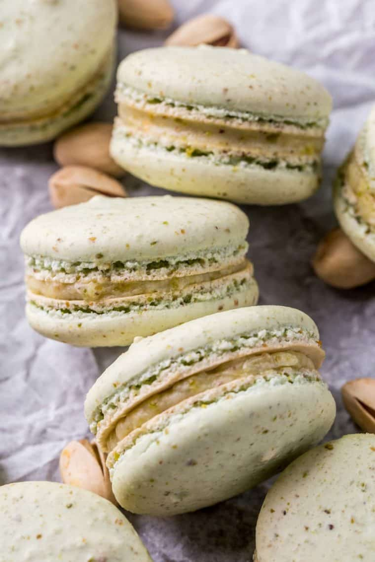 Pistachio macarons laid out next to each other next to pistachios.