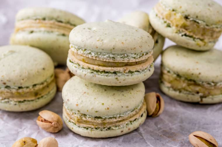 Macarons stacked on top of each other next to pistachios.