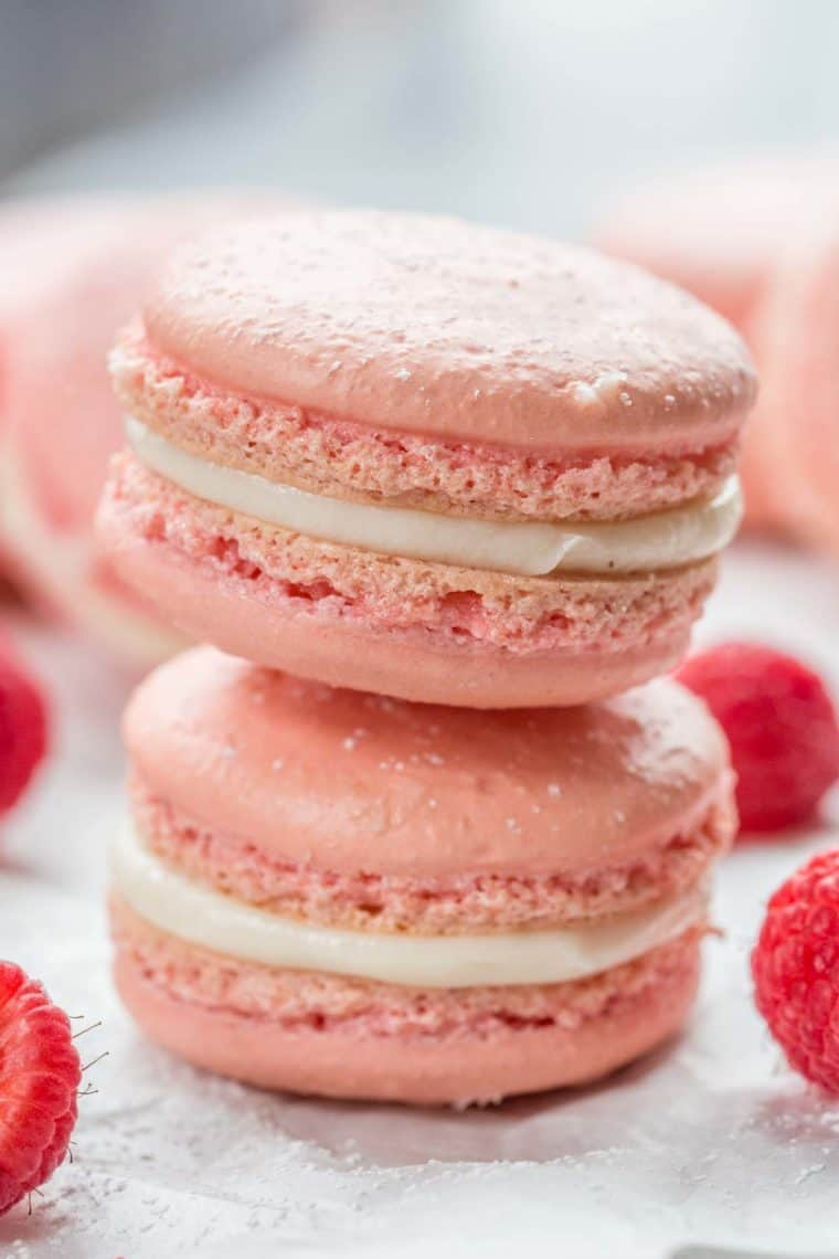 Two raspberry macarons stacked on top of each other sprinkled with powdered sugar and net to fresh raspberries.