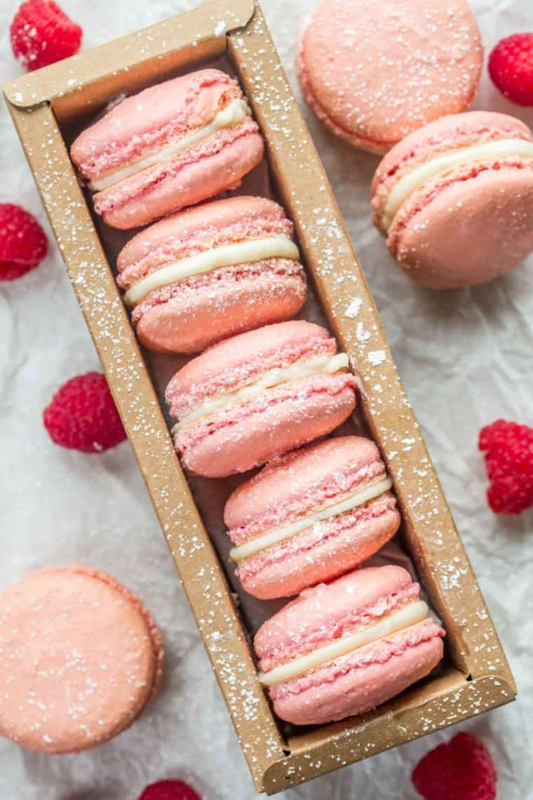 Raspberry macarons laid out in a brown container topped with powdered sugar next to macarons and fresh raspberries.
