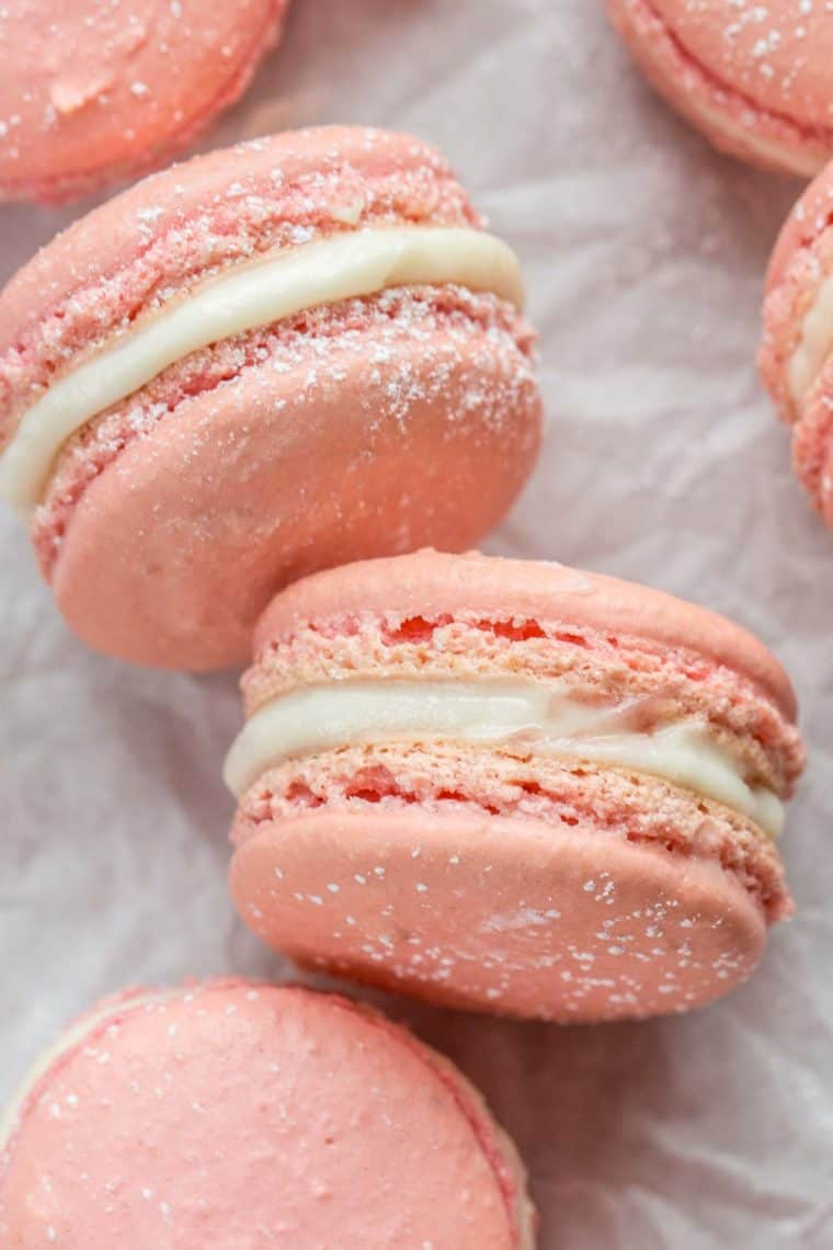 Raspberry macarons laid out on white parchment paper topped with powdered sugar.