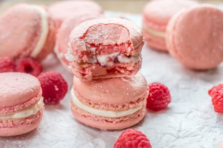 Raspberry macarons on white parchment paper with two stacked on top of each other with one bitten into.