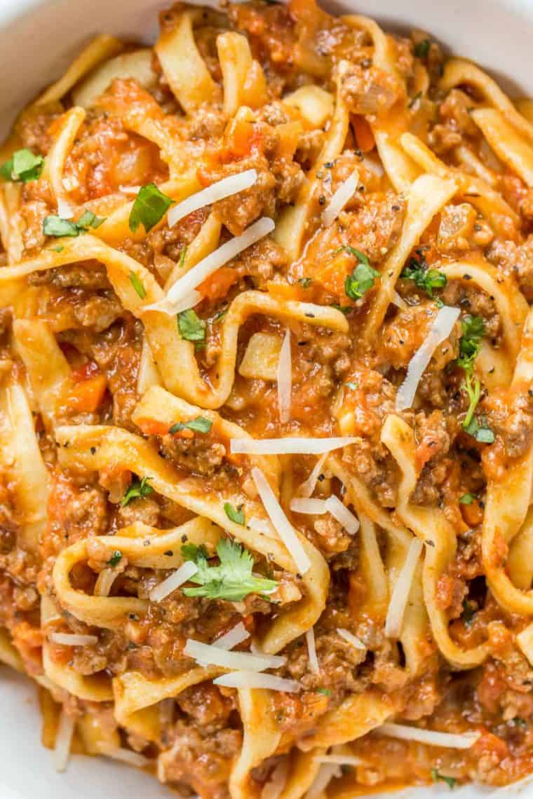 Bolognese pasta topped with cheese and greens.