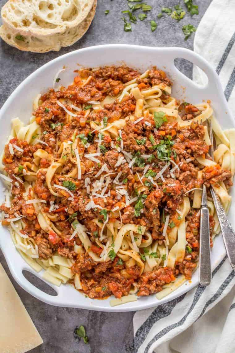 Bolognese pasta in a white bowl topped with parmesan cheese and fresh greens.