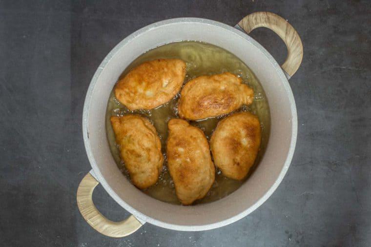 A pan full of frying piroshky.