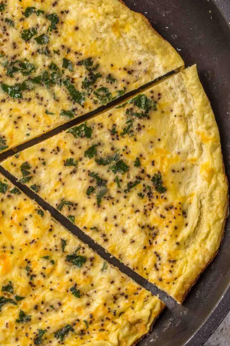 Egg frittata in a black skillet with the frittata slices topped with cilantro and black pepper.