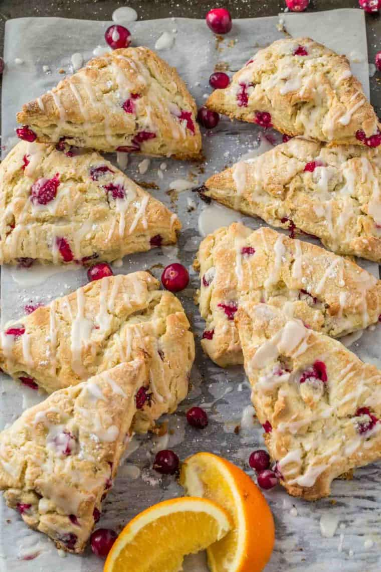 Cranberry scones stacked on top of each other with icing on a baking sheet.