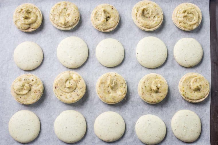 Assemble pistachio macarons laid out on a baking sheet.