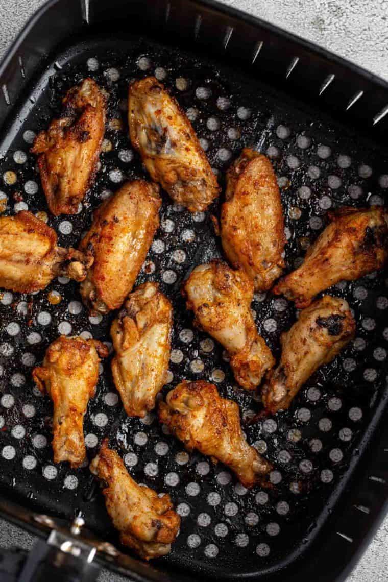 Crispy baked chicken wings in the air fryer rack.