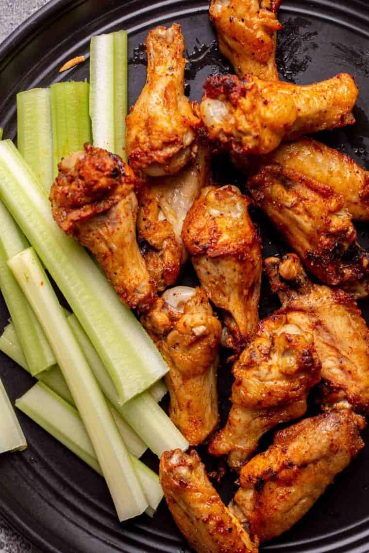 Crispy chicken wings on a black plate next to sliced celery.