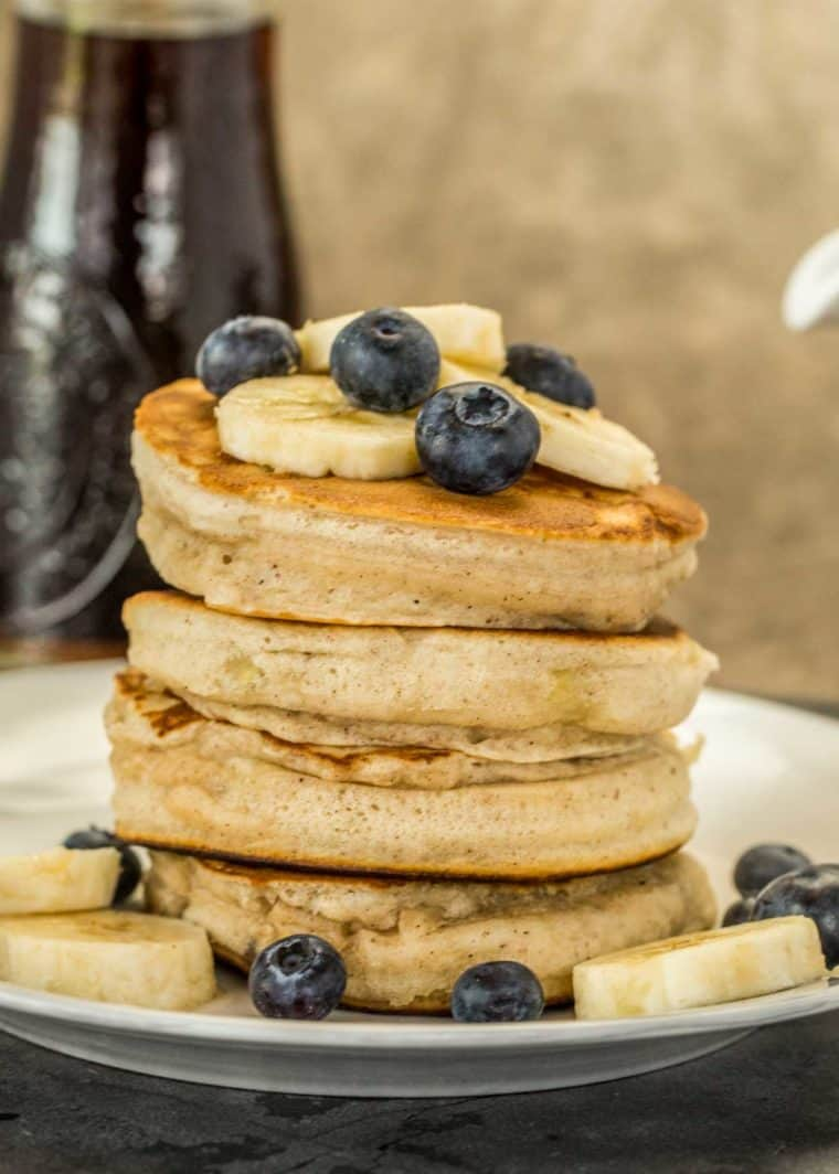 Banana pancakes stacked on top each other topped with blueberries and banana slices.