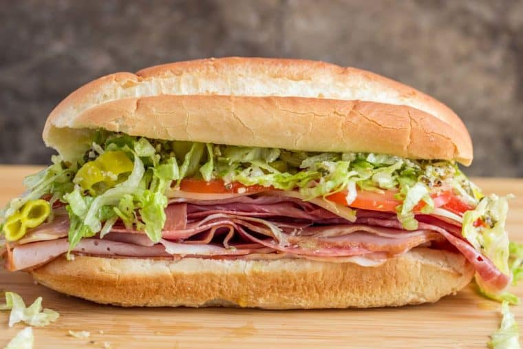 Italian sub sandwich on a cutting baord loaded with meat, cheese, lettuce, and tomatoes!