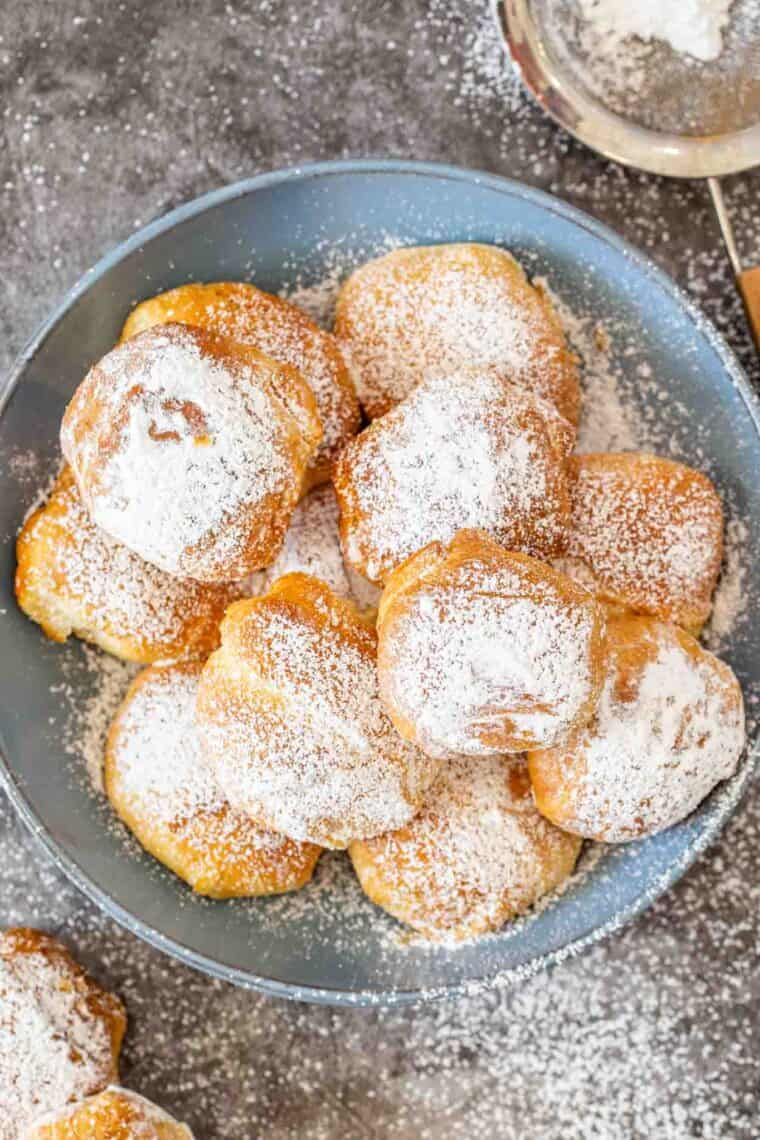 Air fried Oreos in a blue bowl dusted with powdered sugar and a sieve on the side of the bowl.