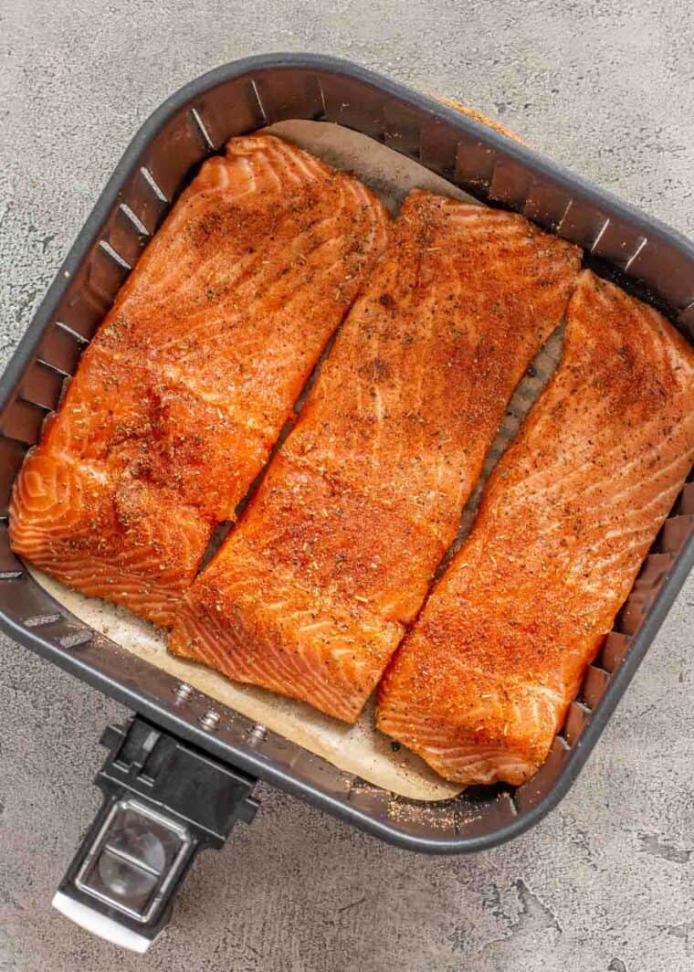 3 salmon fillets in the basket of an air fryer.