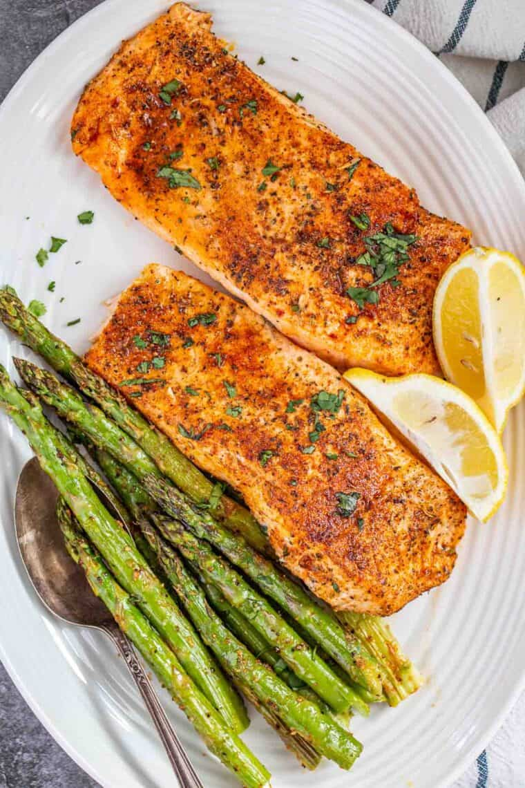 Salmon fillets with asparagus and lemon on a plate.