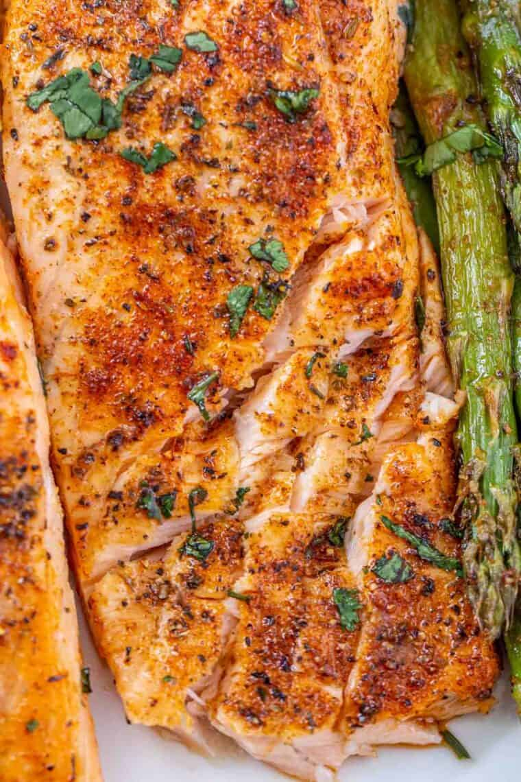Flakey salmon on a plate with asparagus.