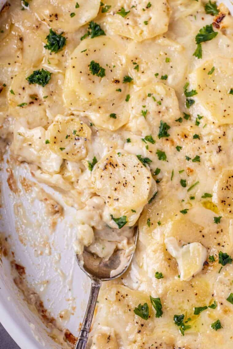 Scalloped potatoes in a casserole dish with a spoon full of potatoes.