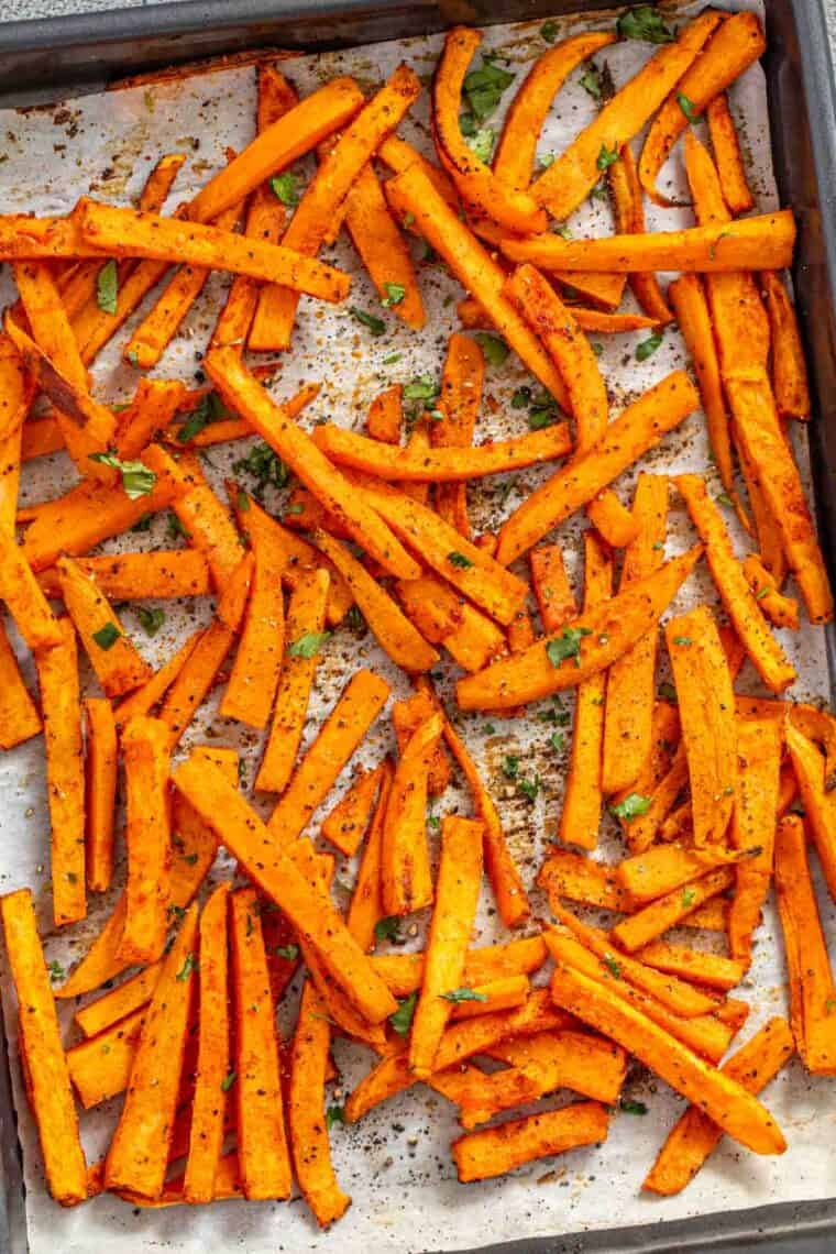 Sweet potato fries in a baking sheet topped with black pepper and chopped greens