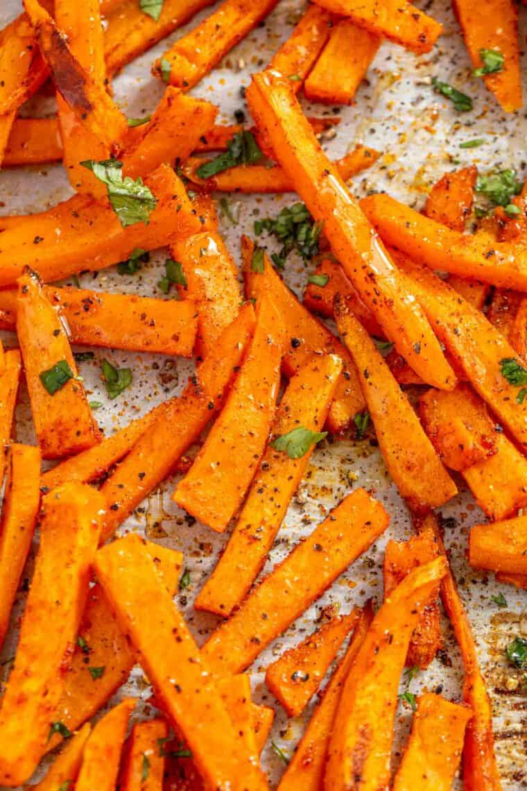 Crispy sweet potato fries laid out on a baking sheet topped with greens and pepper.