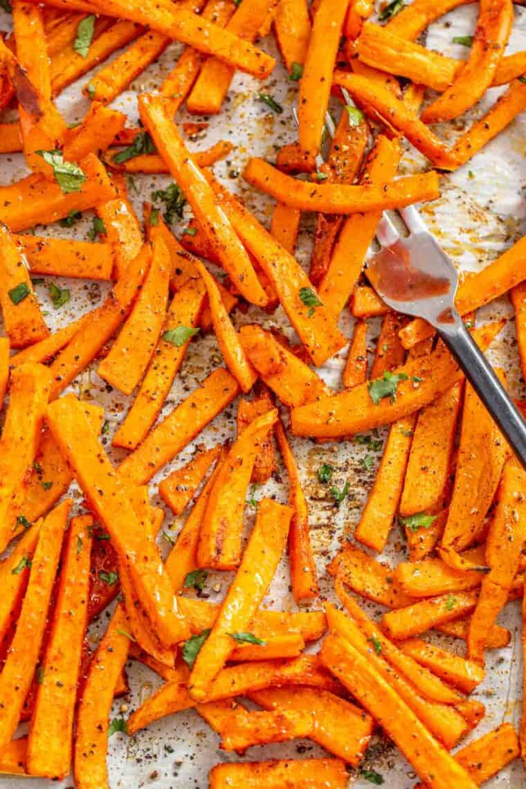 Sweet potato fries on a baking with a fork.
