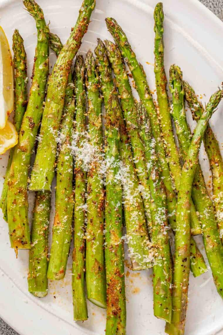 Air fried asparagus on a white plate topped with fresh parmesan cheese.