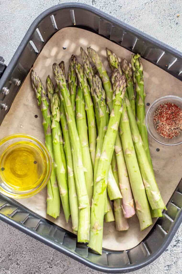Asparagus in the air fryer basket with a small bowl or oil and seasonings.