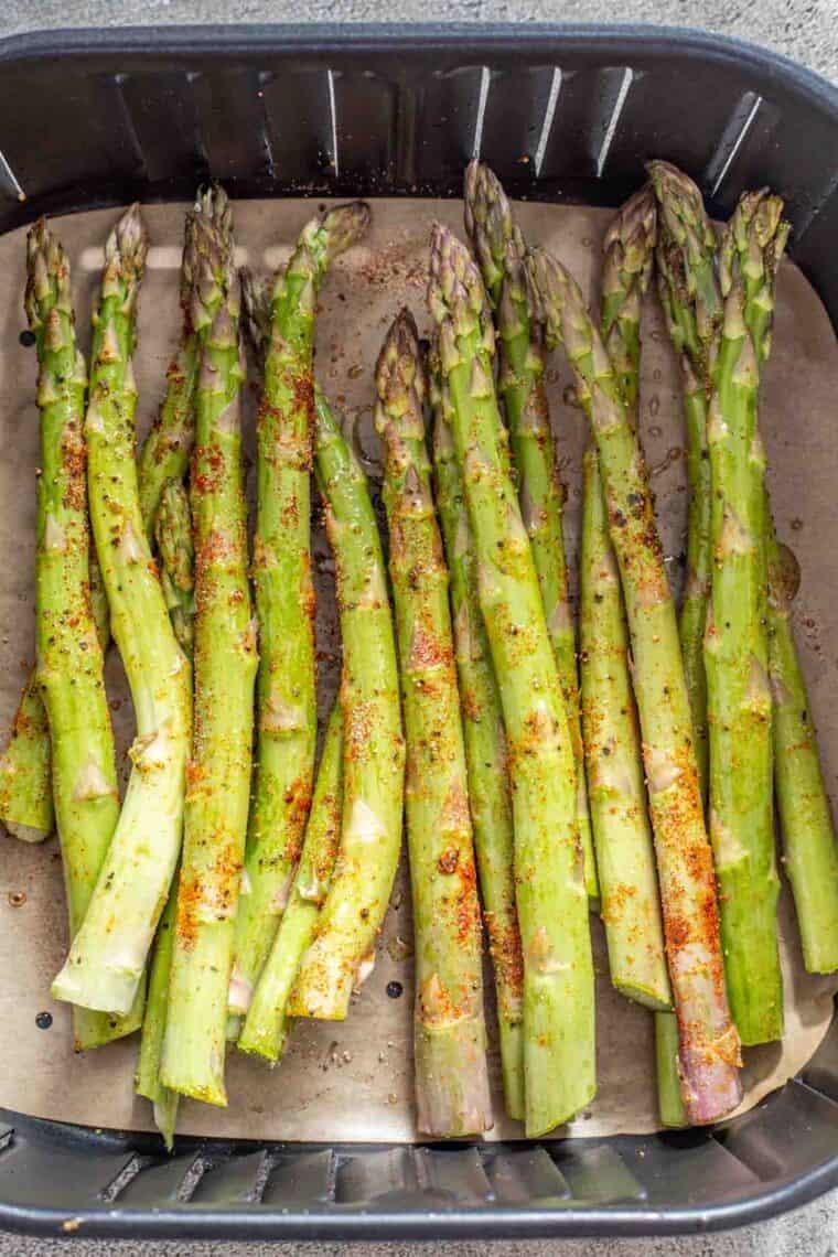 Asparagus tossed in oil and seasonings in the air fryer basket.