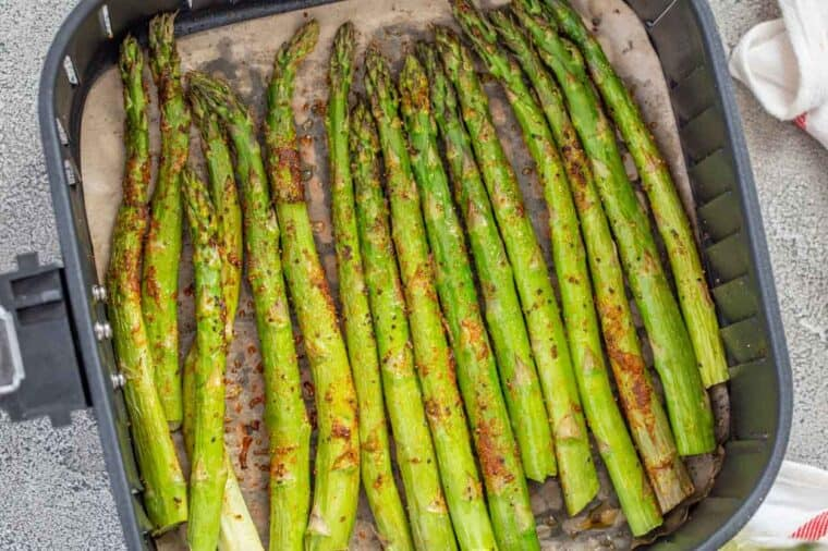 Cooked asparagus in the air fryer basket.