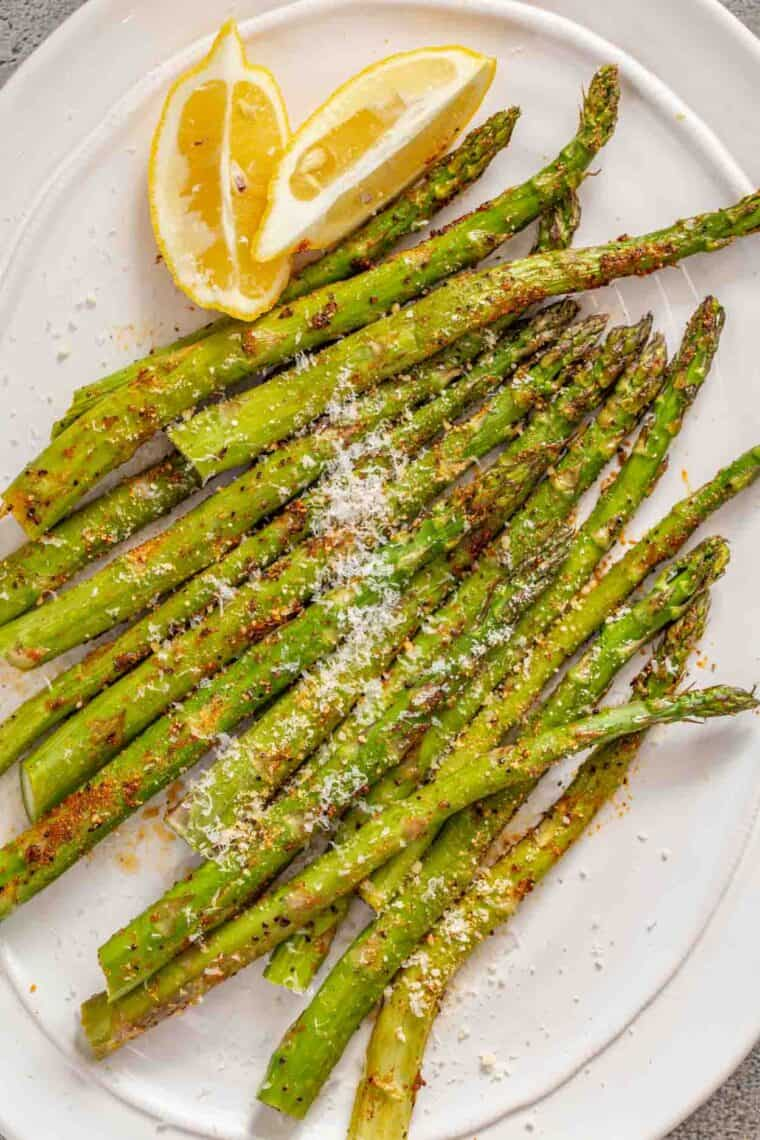 Asparagus topped with grated parmesan cheese on a white plate.