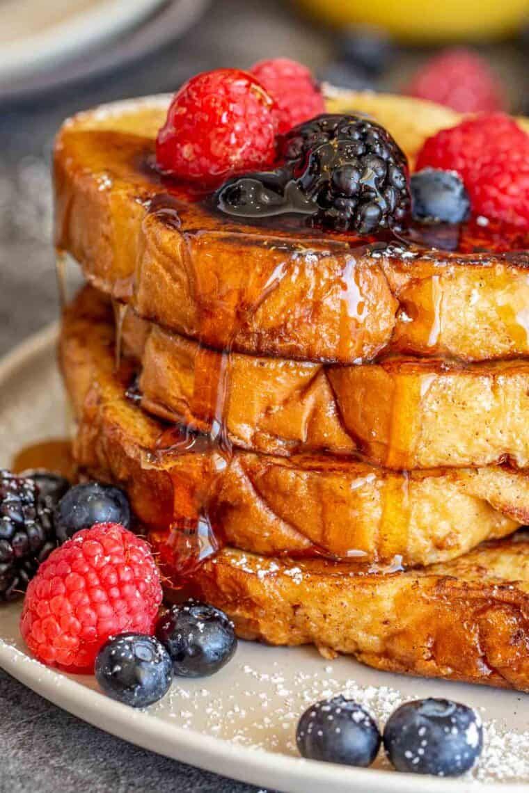 French toast stacked on top of each other drizzled with maple syrup and topped berries and powdered sugar.