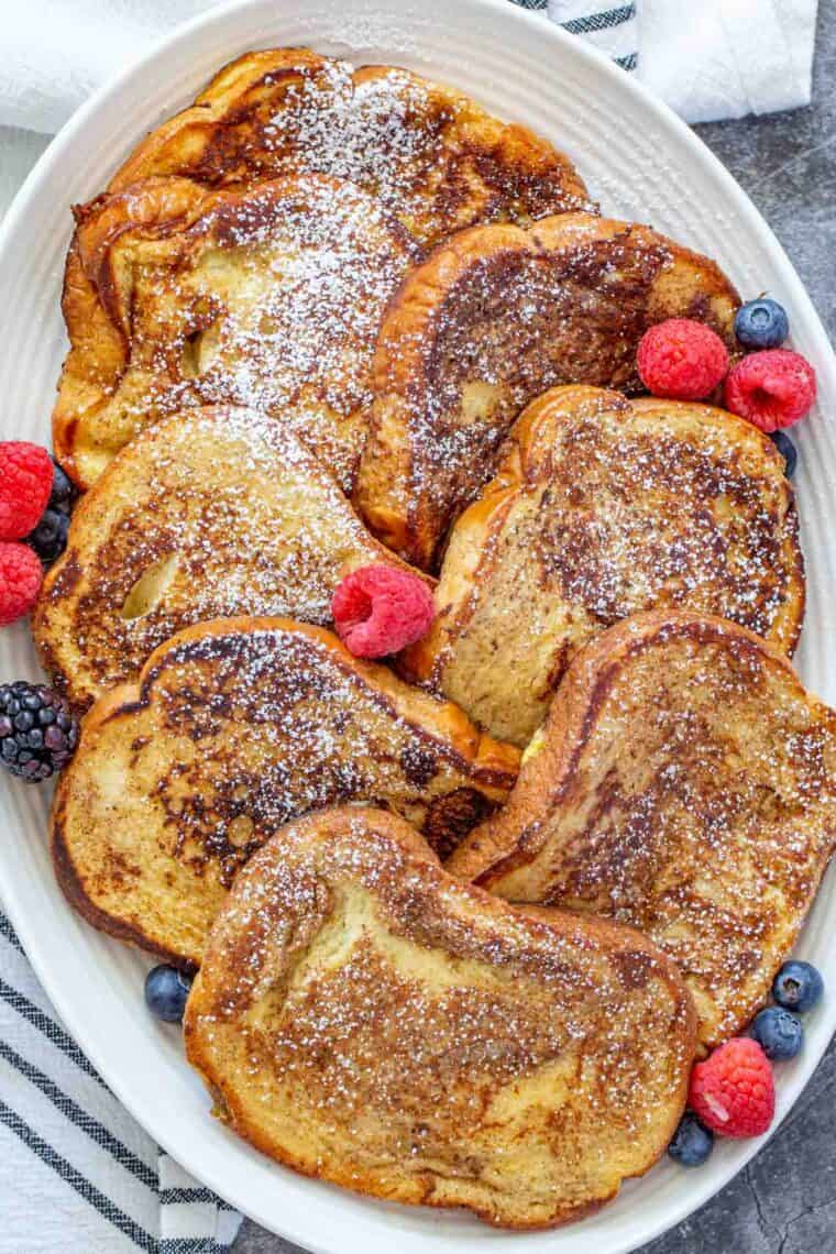 French toast laid out on a white plate topped with powdered sugar and fresh berries.
