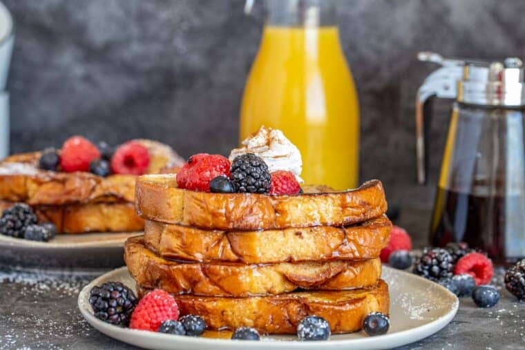 A plate of stacked French toast next to another plate and a jar of orange juice and syrup.