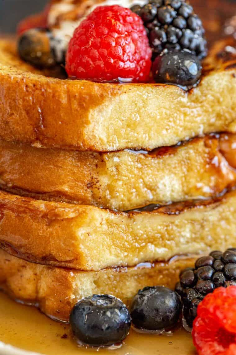 Up close picture of a stack of French toast sliced and drizzled with maple syrup.