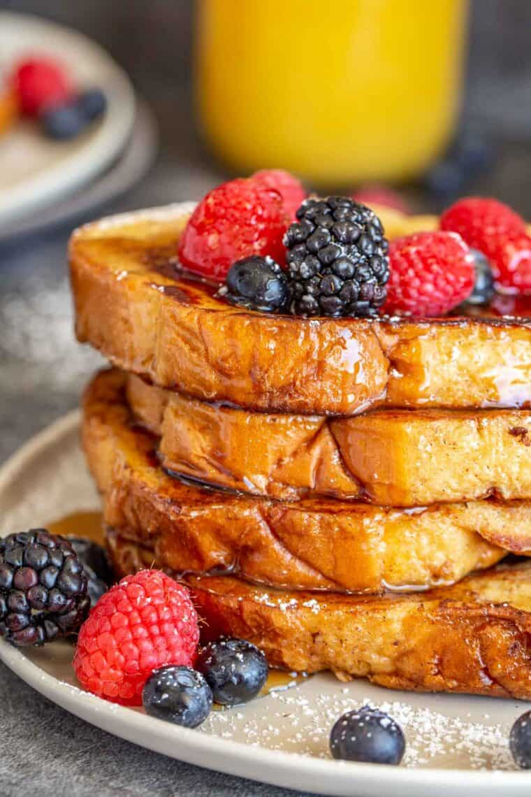 Layered French toast pieces on a plate topped with fresh fruit, powdered sugar and maple syrup.