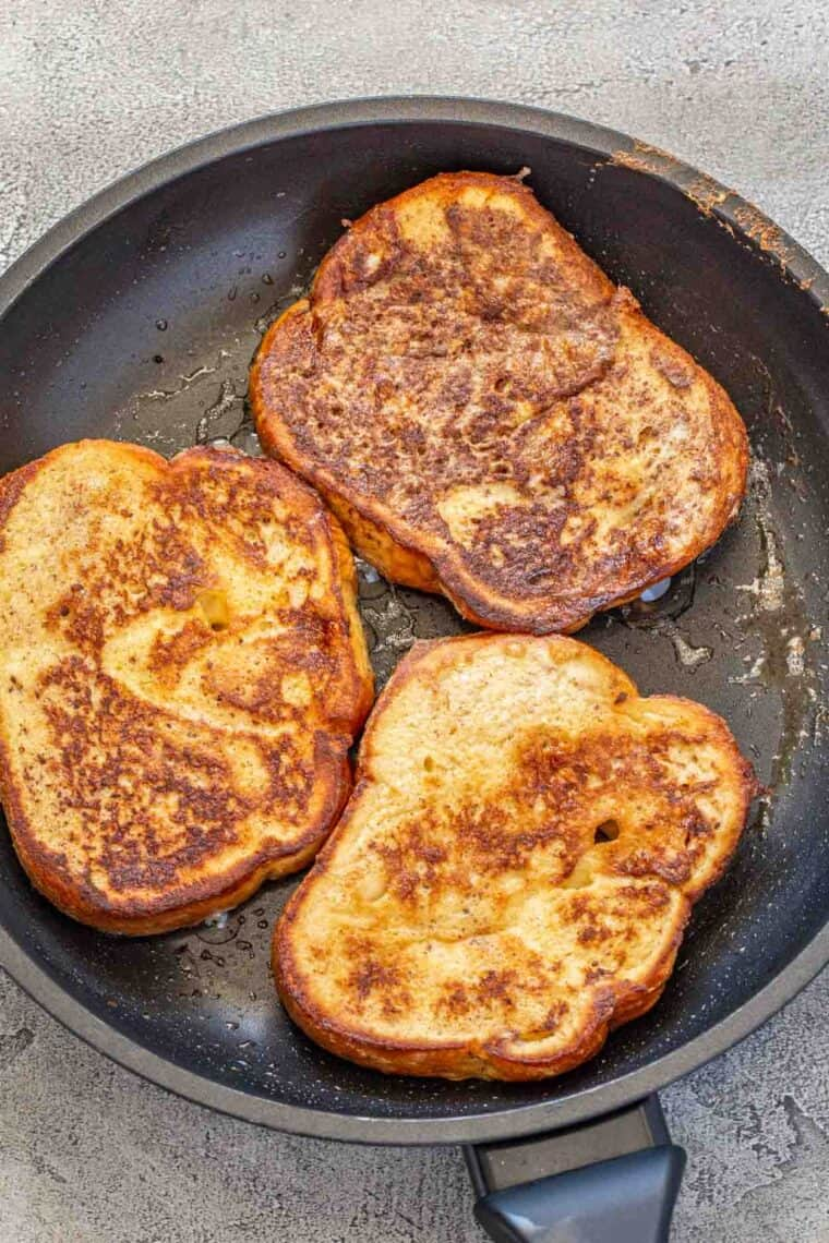 French toast slices in a skillet with butter.