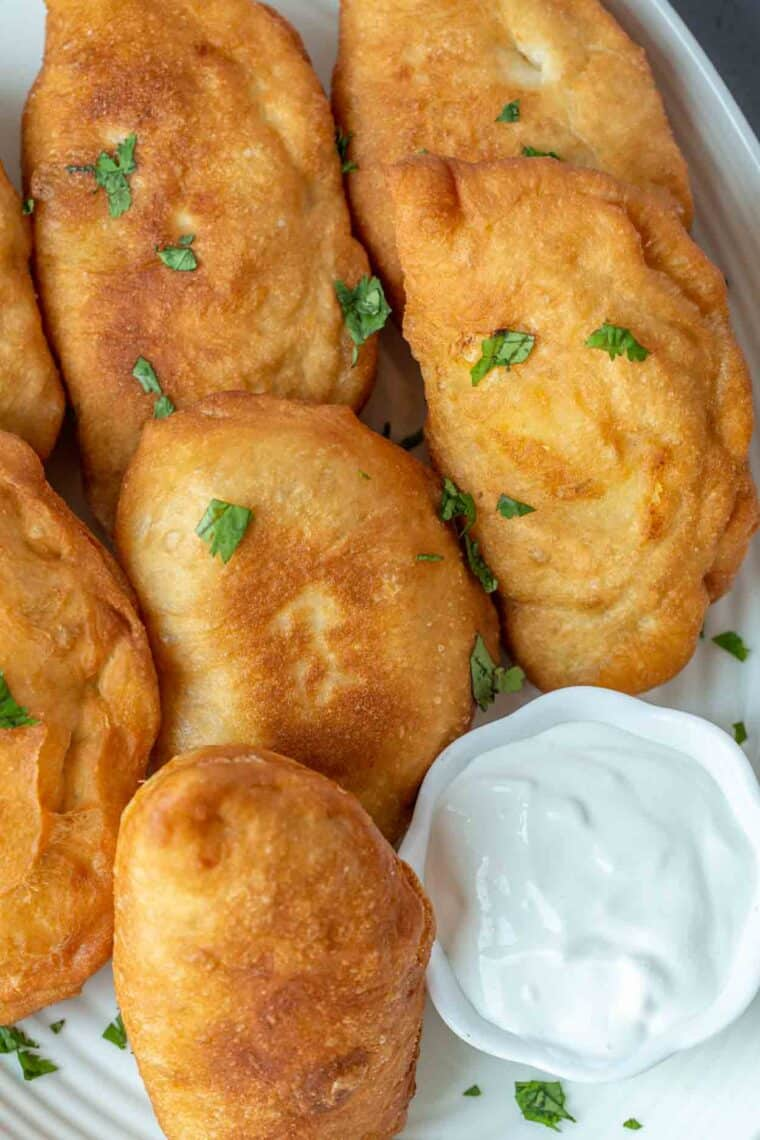 Fried potato pirozhki in a plate next to a white bowl of sour cream.