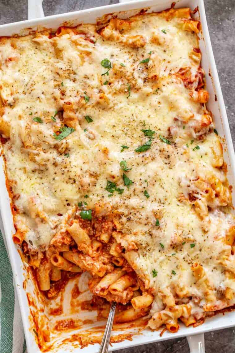 Baked ziti in a white casserole dish topped with fresh chopped greens and black pepper.