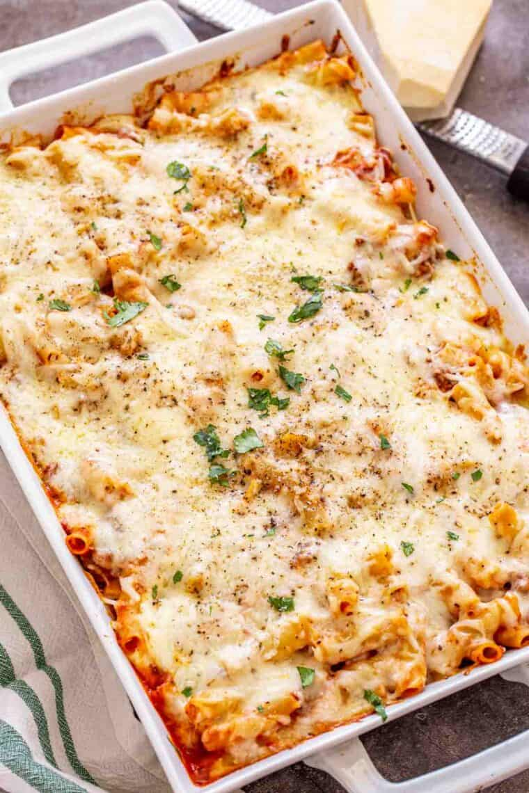 Baked ziti with ricotta cheese on a white casserole dish next to a rag and shredded cheese.