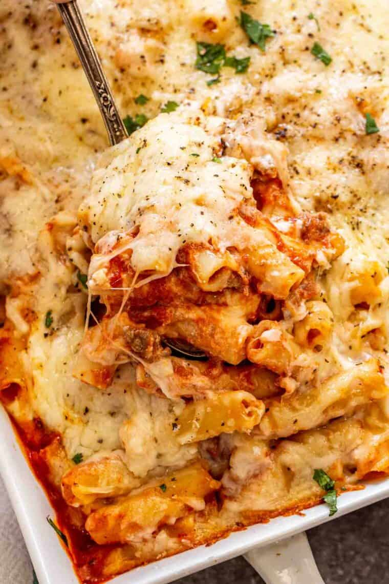 A spoon full of baked ziti with ground beef, cheese and sauce.