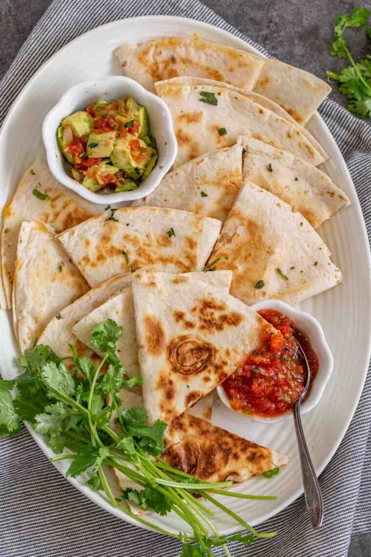 Cheese quesadillas cut into slices on a white plate with guac and salsa topped with fresh greens.