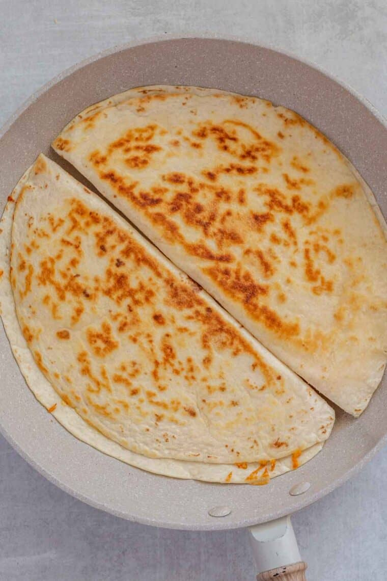 Two tortillas for cheese quesadillas in a skillet cooking.