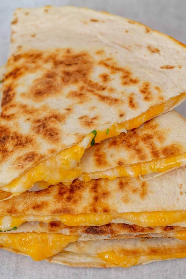 Cheese quesadillas stacked on top of each other with the cheese oozing.
