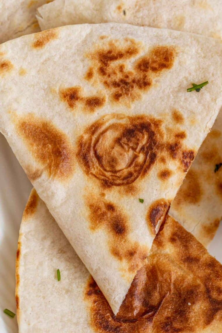 Cheese quesadilla cut up into a triangle filled with shredded cheese and topped with chopped greens.