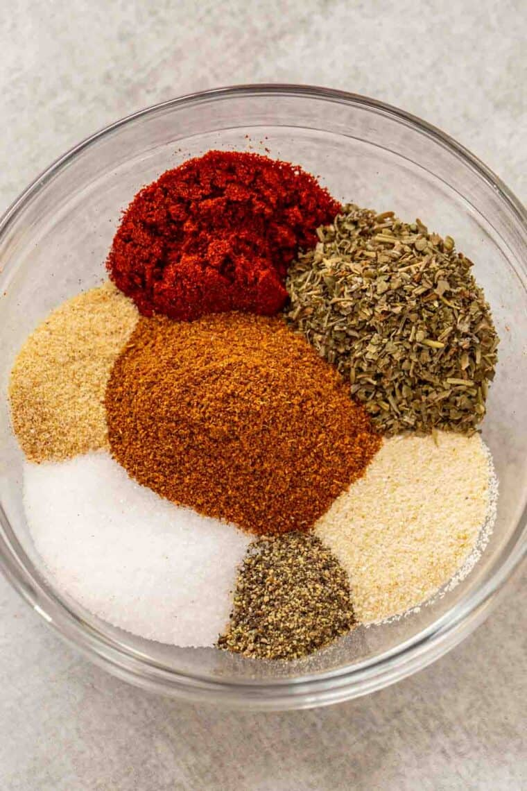All the seasonings needed for this homemade cajun seasoning recipe laid out in a glass bowl.