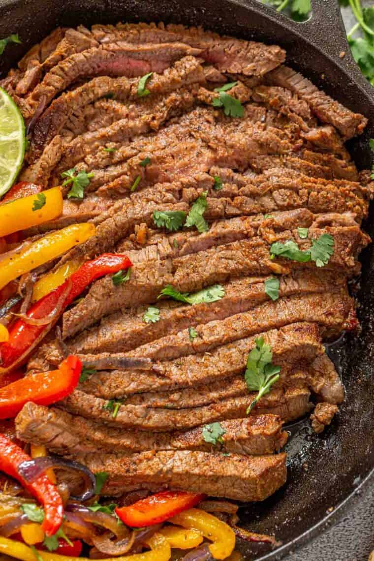 Sliced up beef fajitas topped with chopped greens in a black skillet.