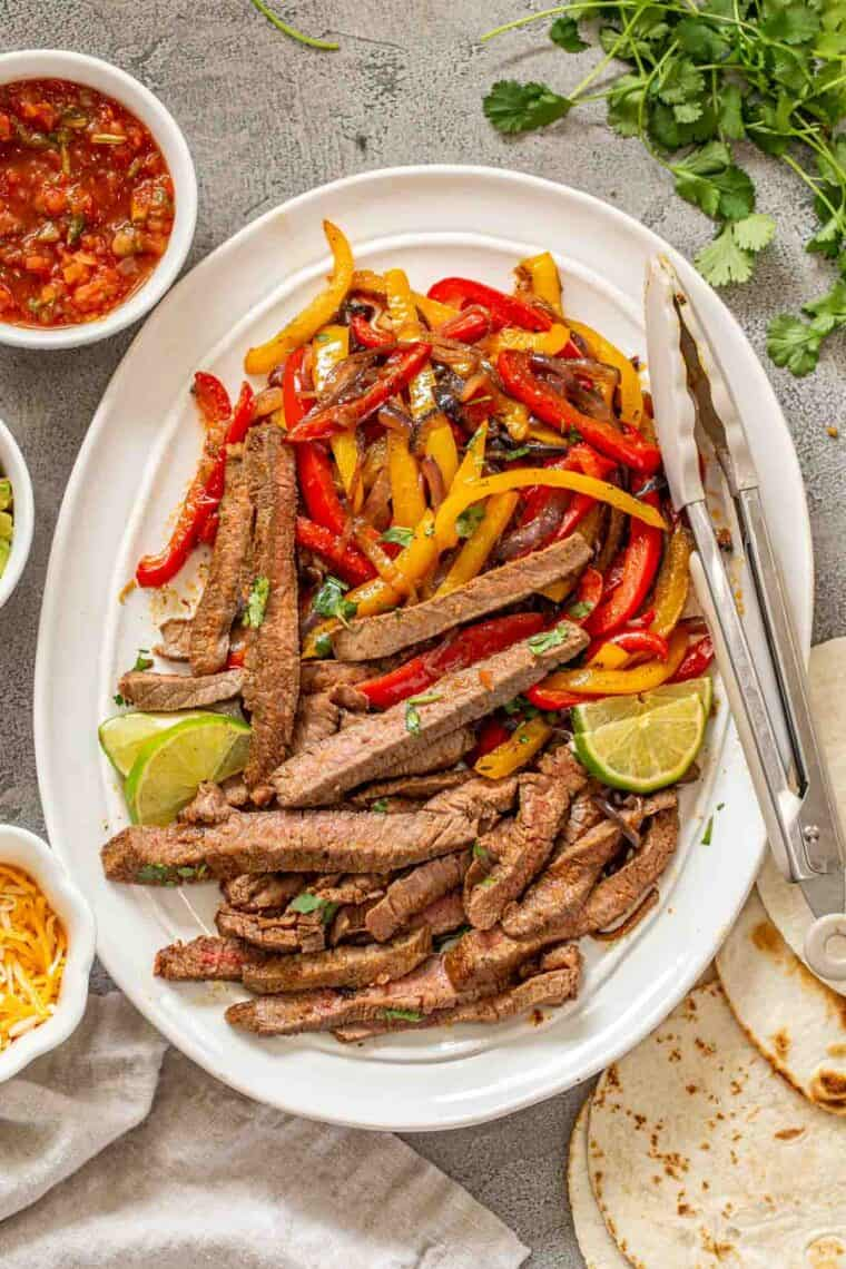 Sliced steak and veggies on a white plate with tongs next to fajita toppings.