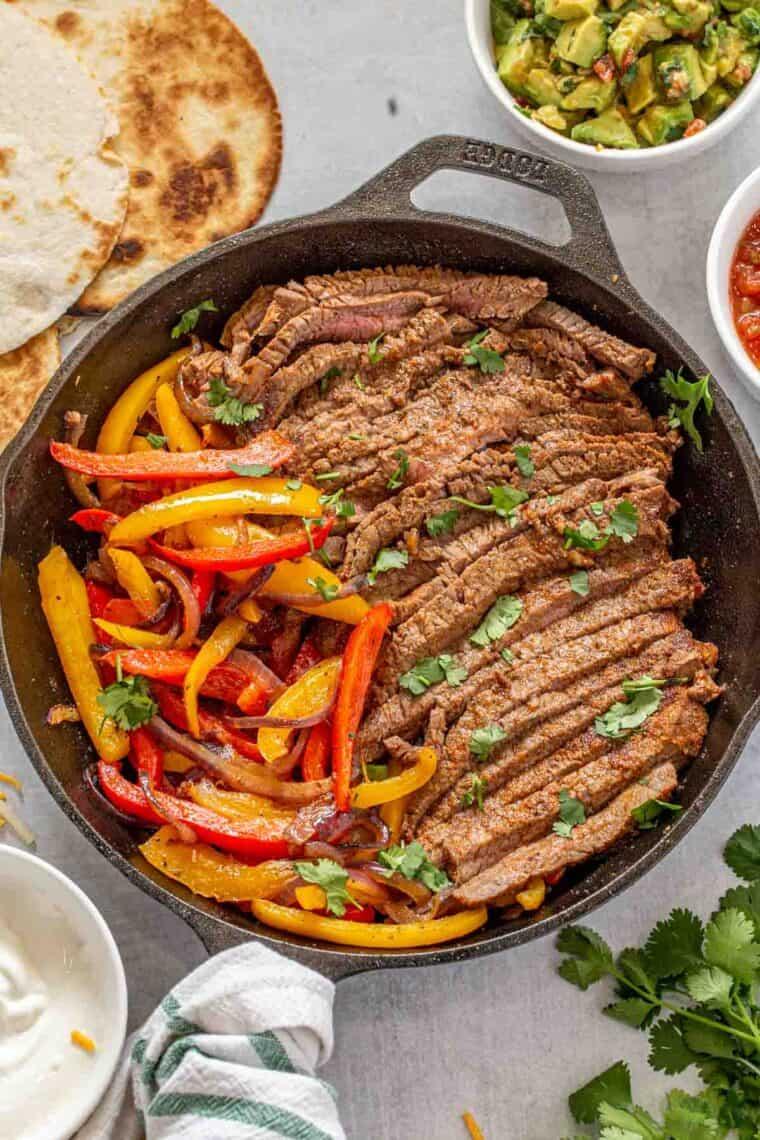 Steak fajitas in a skillet next to toppings for fajitas.